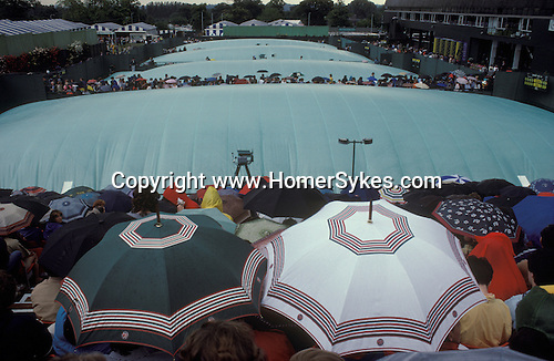 Tennis Wimbledon outside courts with rain covers pulled across courts. Rain stops play. London SW19 UK 1980s.
