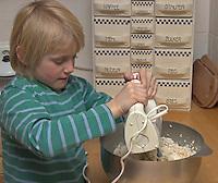 Kinder basteln Blattkacheln aus Salzteig, Junge verrührt die Zutaten zum Salzteig in einer Schüssel