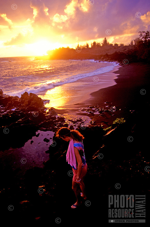 A woman looks into a lava tidepool on the Puna coast with a gorgeous golden sunset in the background.