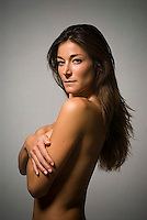 Topless woman with arm over her breasts