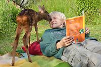 Rehkitz, Reh-Kitz, verwaistes, pflegebedürftiges Jungtier wird in menschlicher Obhut großgezogen, Kind, Junge liegt im Garten auf einer Decke und liest ein Buch, Kitz kommt zum schmusen und spielen, Tierkind, Tierbaby, Tierbabies, Europäisches Reh, Ricke, Weibchen, Capreolus capreolus, Roe Deer, Chevreuil
