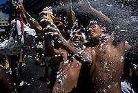 Young men have fun throwing foam to each other during street Carnival in Rio de Janeiro, Brazil. canned foam, foam jet, entertainment, diversion, amusement, recreation