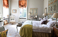 Festoon blinds in a coral coloured fabric adorn the elegant windows of the master bedroom