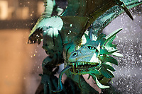 Close-up of a beautiful green dragon fountain head and water drops, with blurred yellow houses in the background, in Braga, Portugal Europe
