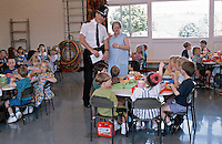 Police officer the youth affairs officer talking to a school dinner lady whilst the children eat their lunch. This image may only be used to portray the subject in a positive manner..©shoutpictures.com..john@shoutpictures.com
