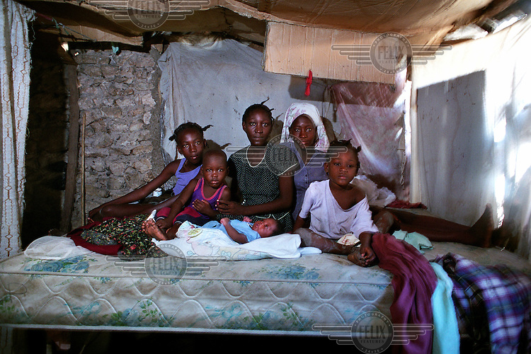 Marianie (centre) with her children and sisters..Baby Wilklef was born on the same day that Gonaives was flooded. After Marianie gave birth they left the hut to climb on the roof of a nearby house. One of the walls of the hut is completely destroyed. Marianie's mother went to the market that day and never came back..Three weeks after tropical storm Jeanne hit Gonaives parts of the city are still flooded. Over 2700 people were reported dead or missing. Haiti is particularly vulnerable to flooding after heavy rainfall due to intense deforestation.