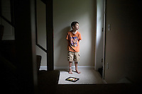 """Jack Ursitti, age 7, poses for a portrait with his iPad in his home in Dover, Mass., on Monday, July 25, 2011. Jack uses the iPad both for leisure activities, such as listening to music and looking at photos of his family, and for educational activities. Jack has been diagnosed with autism.  After school at his home, Jack works with his teacher and a therapist to do educational and independent leisure activities. ..Jack received an iPad for Christmas, according to his mother Judith Ursitti. """"I wanted mine back,"""" said Judith. She had gotten an iPad for her birthday in 2010, and Jack used it constantly. """"There's something intuitive about it,"""" said Judith.  In the beginning it was just a distraction, """"but now we're moving to use it for an educational purpose,"""" she said...Jack Ursitti wears a small GPS ankle bracelet at all times in case he runs off from his family or caretakers. The device will be activated if he goes missing, allowing police and other searchers to find him."""