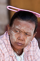Myanmar, Burma.  Burmese Woman with Comb in her Hair Wears Thanaka Paste on her Face as a Cosmetic Sunscreen.  Nyaung Oo, near Bagan.