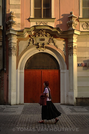A woman walks past the doorway of a building with baroque architecture and decoration near Old Town square in Prague, Czech Republic on 14 May 2007.