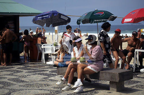 Ipanema Beach, Rio de Janeiro, Brazil. Two women drinking from fresh coconuts at a beach-side bar.