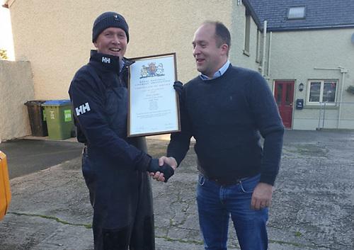 Lough Derg RNLI crew member Chris Parker presents a framed Certificate of Service to former helm Peter Clarke