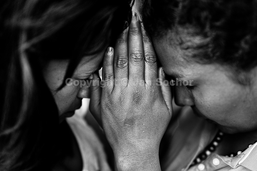 Colombian women, having joined hands, pray during the religious healing ceremony performed at a house church in Bogota, Colombia, 28 January 2013. Hundreds of Christian belivers, joined in nameless groups, gather every week in unmarked home churches dispersed in the city outskirts, to carry out prayers of liberation and exorcism. Community members and their religious activities are usually conducted by a charismatic pastor or preacher. Using either non-contactive methods (reading religous formulas from bible, displaying Christian symbols and icons) or rough body-pressure-points techniques and forced burping, a leading pastor commands the supposed evil spirit, which is generally believed to come from witchcraft, to depart a person's mind and body. The demon's expulsion often consists of multiple rites and may last for several months.