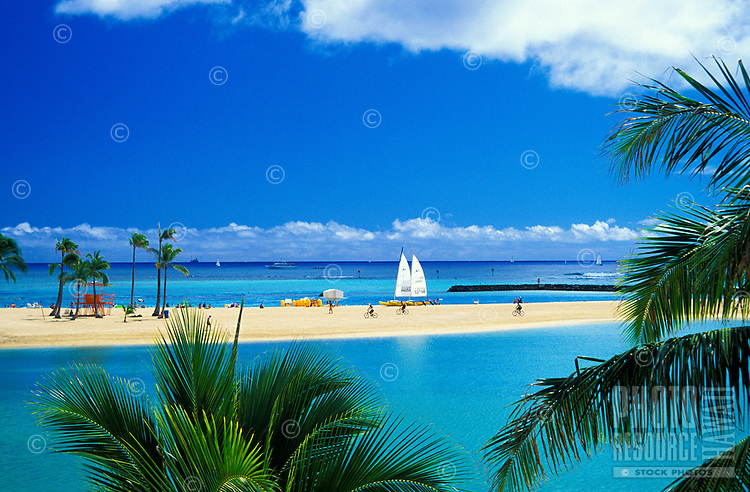 View of renowned Waikiki Beach with it's warm sands, blue waters, resort hotels and swaying palm trees. This photo taken at the lagoon behind the Rainbow Hilton Hotel.