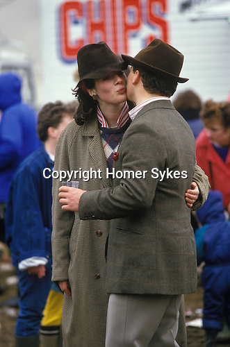 Badminton, Gloucestershire. 1980's<br /> No sex please we're very British, a couple politely air kiss. Coincidentally co-ordinated in his-n-hers matching red-stripped shirts, tweed jackets and almost battered brown trilby hats. Looking suitable fashionable while attending the annual horse trials.