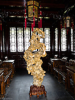 Golden strone sculpture (not gold).  Used as a decorative piece inside the home to help achieve inner peace and balance.  Yu Gardens, a peaceful place to escape the bustle of Shanghai.  Full of visitors, still very calming.  Details in the buildings, doors and stone sculptures.  Helps get your Ying and Yang in balance.
