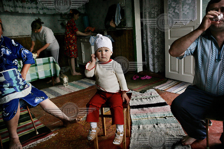 A small child takes centre stage during a family gathering in the village of Dezghingea in Gagauzia an autonomous region of Moldova..
