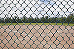 View from behind home plate in baseball diamond, Centenial Park, Federal Way, WA.  A public park with athletic fields..Looking center field from behind home plate.  Fence in foreground. This image available for license through exclusive agency.  Please contact the photographer