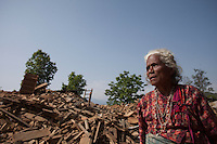 An elder woman stands in front of her collapsed house at Dhulikhel, outskirt of Kathmandu, Nepal. May 1, 2015