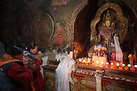 Women pray at an altar in the Hemis Monastery.