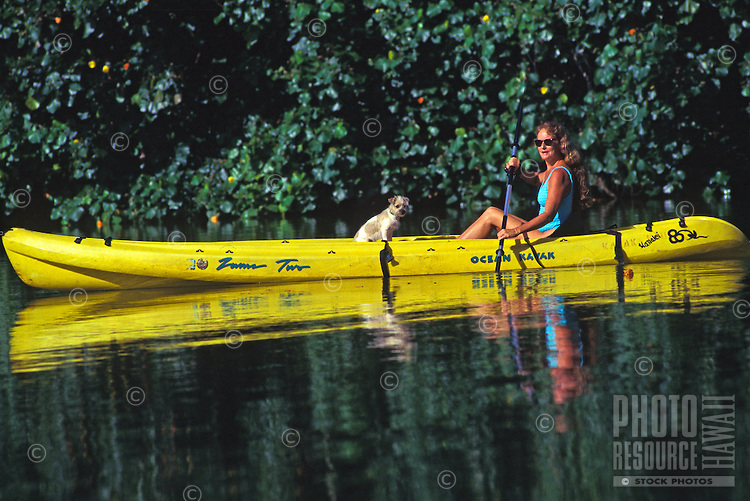 Woman and her best friend paddle a kayak along the Hanalei River, Kauai