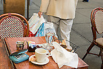 Memory forgetfulness woman in 40s leaving wallet on table of sidewalk  cafe walking off with shopping bags