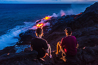Visitors view the spectacular sight of lava flowing down a cliff and into the ocean after dusk, Hawai'i Volcanoes National Park, Hawai'i Island.