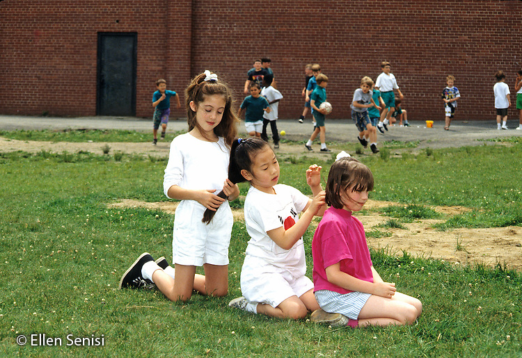 MR / Schenectady, NY.Howe International Magnet School / Grade 3.Three girls (age 8; one Korean-American) play with each other's hair on playground at recess. In the background, boys are actively playing..MR: Wil3, Row2, Obr3.FC#: 26674-00114.scan from slide.© Ellen B. Senisi