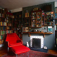 A retro style red armchair and footstool are placed in front of bookshelves which line the walls. A simple fireplace is set in a grey painted wall with a wooden shelf as a mantelpiece.