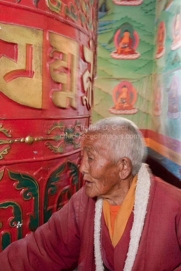 Bodhnath, Nepal.  Buddhist Worshiper Turning Prayer Wheel, Tsamchen Gompa.
