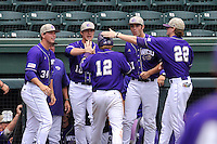 Right fielder Bryson Bowman (12) of Western Carolina is congratulated by teammates after scoring a run against Mercer in Game 1 of the SoCon Tournament championship final series on Sunday, May 29, 2016, at Fluor Field at the West End in Greenville, South Carolina. Western won, 4-2. (Tom Priddy/Four Seam Images)