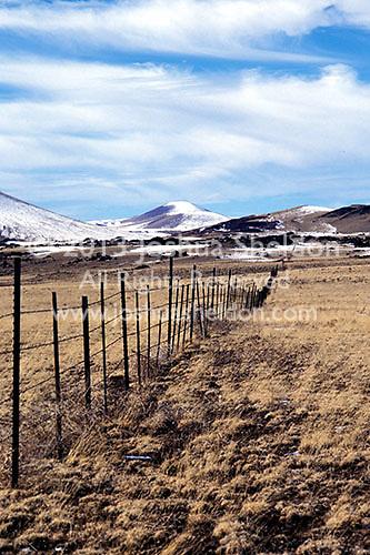 Border fence crossing desert landscape towards snow covered mountains<br />