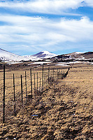 Border fence crossing desert landscape towards snow covered mountains<br />