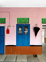 The walls of the veranda are painted in the same pink as the interior of the house and the woodwork picked out in royal blue