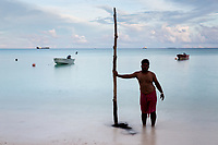 """Aloito Vaivasa, 26, a fisherman, stands near the shoreline in central Funafuti, the capital of the small Pacific nation of Tuvalu. Land poor micro-states in the region are some of the most vulnerable to climate change impacts. This has driven many to flee their homelands, in fear of the potential environmental catastophes their countries are vulnerable to, and also in search of higher incomes through better job opportunities provided by other larger countries. It is estimated nearly 20% of Tuvalu's population have left and reside in other countries such as New Zealand and Australia. Young adults are the most likely to leave, with the older generation most likely to stay. A recent report by The Australian National University estimates by 2050, """"47% of Tuvaluan adults (4,900 people)...will want to migrate but [will] be unable to do so"""", with limiting factors being financial and available places on migration programs to other countries."""