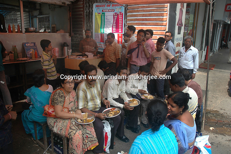 Office workers having meal during break at  a street food stall in New market area of Kolkata. Street food stalls are serving the office goers for decades. All kind of Indian foods are available on the street at an affordable price. They sale them openly. Street food stalls are another results of unempoloyment and over poppulation. They serve millions of people in India. Kolkata, West Bengal,  India  7/18/2007.  Arindam Mukherjee/Landov