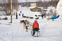 Sebastian Schunelle runs through the village of Kaltag on Sunday morning stopping only long enough to get his food bags and straw during Iditarod 2008