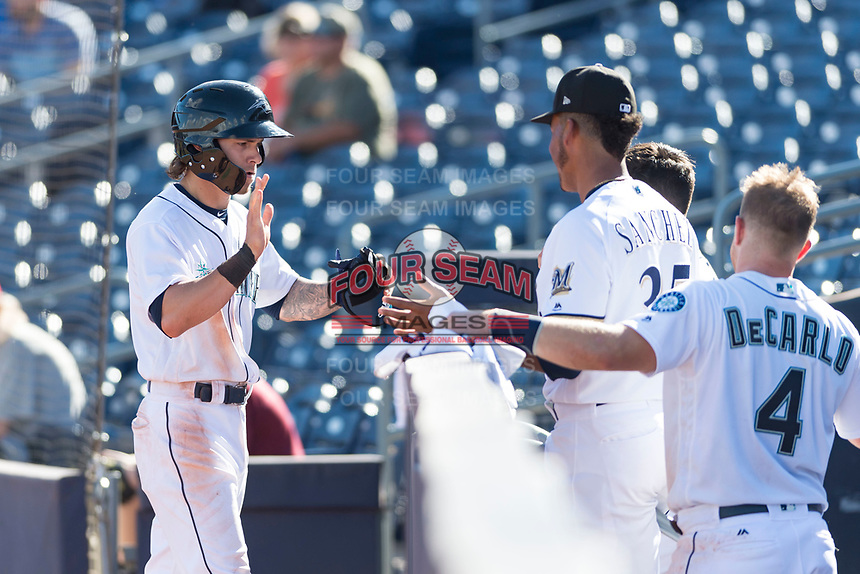 Peoria Javelinas right fielder Ian Miller (9), of the Seattle Mariners organization, is congratulated by Miguel Sanchez (35) and Joe DeCarlo (4) as he returns to the dugout after scoring a run during an Arizona Fall League game against the Glendale Desert Dogs at Peoria Sports Complex on October 22, 2018 in Peoria, Arizona. Glendale defeated Peoria 6-2. (Zachary Lucy/Four Seam Images)