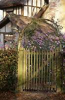 Rustic garden gate with quaint thatched roofed cottage.