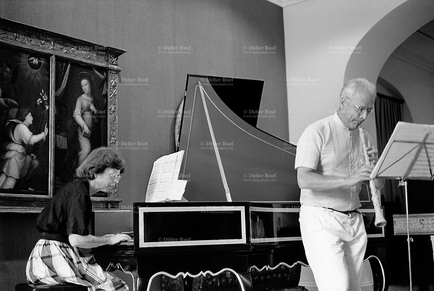 Switzerland. Geneva. Classical music at the Musée d'art et d'histoire. A woman plays the piano and a man the flute during a concert on Music Day. A religious painting is hanged on the wall. The Fête de la Musique, also known in English as Music Day, Make Music Day or World Music Day, is an annual music celebration that takes place on 21 June (but usually during the previous or following weekend). On Music Day the citizens of a city or country are allowed and urged to play music outside in their neighborhoods or in public spaces and parks. Free concerts are also organized, where musicians play for fun and not for payment. 22.05.1993 © 1993 Didier Ruef