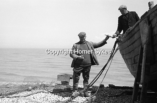 Dungeness, Kent. 1969<br /> Fisherman Charlie Tart working on some light repairs to this boat. The Tart family along with the Olier's are the two most prominent fishing family in Dungeness, they have been living and fishing off the flint shingle beach since the early 20th century<br /> The late Charlie Tart, with colleague in boat  Caption thanks to Mike Golding