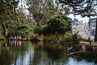 San Francisco, California, USA.  Family Feeding Fish at Stow Lake, Golden Gate Park, an Oasis of Tranquility in the Midst of San Francisco's Traffic and Urban Distractions. 19th Avenue Traffic on Right.