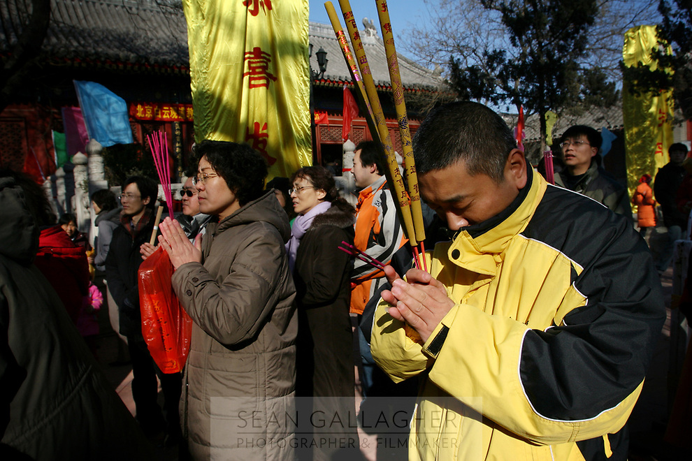 CHINA. Worshippers during Chinese New Year in Baiyun Temple in Beijing.  Chinese New Year, or Spring Festival, is the most important festival and holiday in the Chinese calendar In mainland China, many people use this holiday to visit family and friends and also visit local temples to offer prayers to their ancestors. The roots of Chinese New Year lie in combined influences from Buddhism, Taoism, Confucianism, and folk religions.  2008