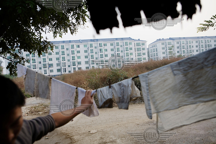 A villager's home overlooking a new residential estate on Beijing's fifth ring road, where new urban construction meets the countryside. Here villages and farmlands are being pushed out to make way for new developments.