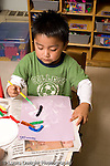 Preschool ages 3-5 art activtity gluing collage made of pipe cleaner pieces on paper vertical boy at work