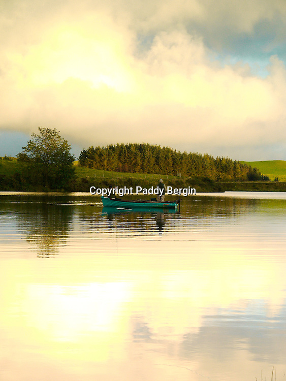 This photo was taken at Llyn Frongoch in close proximity to the village of Trisant, close to the Aberystwyth to Devil's Bridge road. Frongoch is a fly only lake and is regularly stocked with both brown and rainbow trout. The quality of fish is excellent and boats are available. At Frongoch, Aberystwyth Angling Association have two caravans for hire for visitors wishing to stay in the area and take advantage of the fishing in this small but delightfully situated lake. Admist wonderful upland scenery, close to the Rheidol and Ystwyth valleys, and just twelve miles from the coast at Aberystwyth they represent excellent value for anyone wishing to combine angling with a family holiday. <br /> <br /> Stock Photo by Paddy Bergin