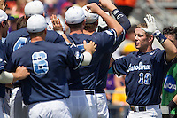 North Carolina catcher Brian Holberton (10) is greeted at by his teammates in the dugout after he hit a 3 run home run in the first inning against the Louisiana State Tigers during Game 7 of the 2013 Men's College World Series on June 18, 2013 at TD Ameritrade Park in Omaha, Nebraska. The Tar Heels defeated the Tigers 4-2, eliminating LSU from the tournament. (Andrew Woolley/Four Seam Images)
