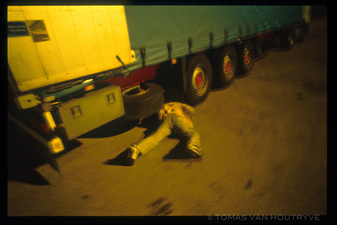 Abdhamid, a Palestinian refugee crawls under the wheels of a semi truck in Calais, France on Oct. 14, 2003. Each night dozens of refugees attempt this risky method to get from France to Great Britain. The refugees hide in and under trucks that later board ferry boats headed to the U.K.