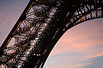 As the sun sets on the Eiffel Tower in Paris France, visitors climb the stairs in the towers base. The intricate structure is sillouetted against a pastel sky.