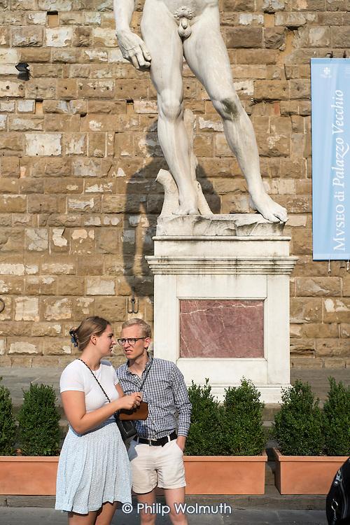 Tourists in front of a replica of Michelangelo's David, Piazza della Signoria, Florence, Italy
