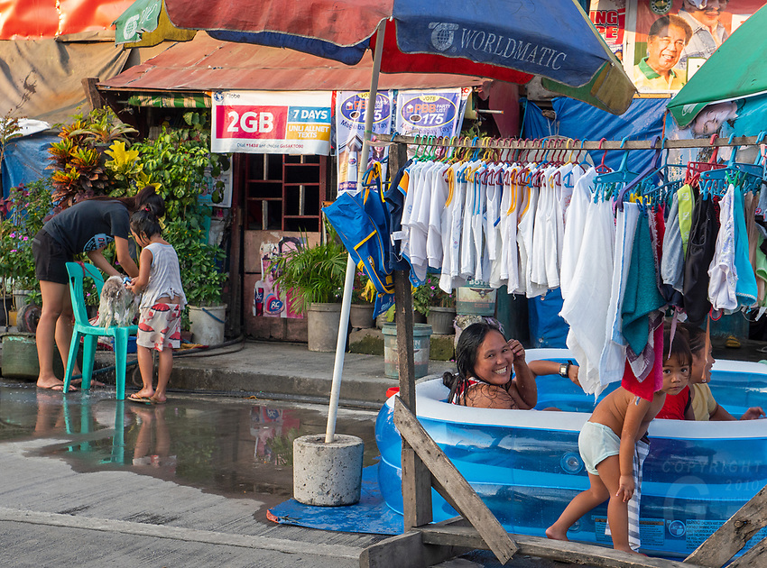 Street Photography, Manila, Philippines Family escaping the summer heat in the city in a plastic pool in the streets of Tondo,